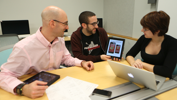 From left, Adam Peruta, assistant professor in the department of strategic communication, points to a Chipotle app as junior Noah Delin looks on. 