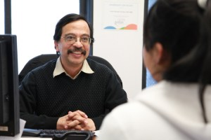 Mario Ayala sits with a client in his office at IRS-BC, where he eases the integration of refugees and new immigrants in Canada. Photo by Elton Hubner
