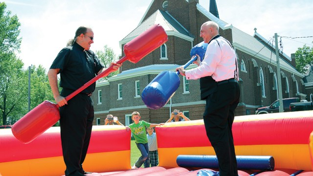 Father Dan Gardner, pastor of St. Leo Parish in Horton, and Archbishop Joseph F. Naumann prepare to square off in a friendly game of joust. The jousting arena was one of many special activities set up to celebrate the 100th anniversary of the church building on May 22.