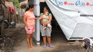 Enma Vera, left, a Catholic Relief Service coordinator in Ecuador, talks with Karina Zeballo outside the tent where she lives because her house was damaged during country's earthquake April 16. Although reconstruction is under way, many families continue to live in tents provided by Catholic Relief Services and Caritas Internationalis. (CNS photo/Barbara Fraser)  See ECUADOR-EARTHQUAKE-REBUILD Aug. 22, 2016.
