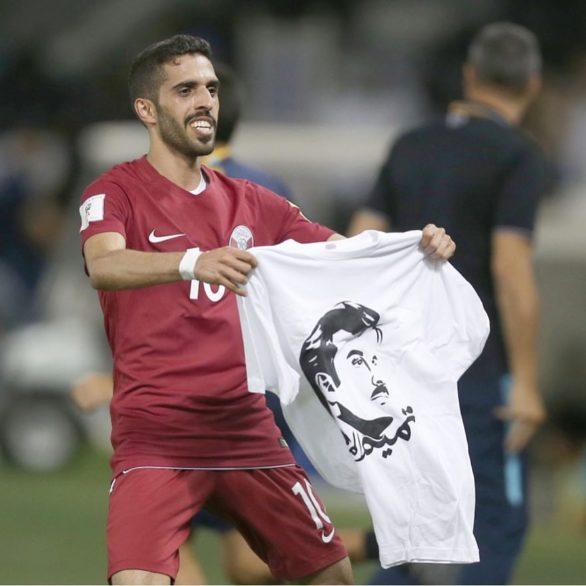 Qatari player Hasan Khalid AlHaydos waving a Tamim Al Majd T-shirt after scoring