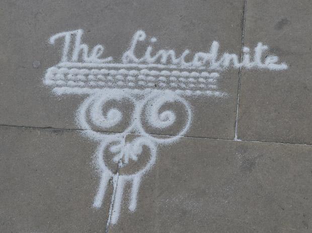 Rangoli artist Janak Chauchan writes The Lincolnite in marble power. Photo: Dale Benton for The Lincolnite
