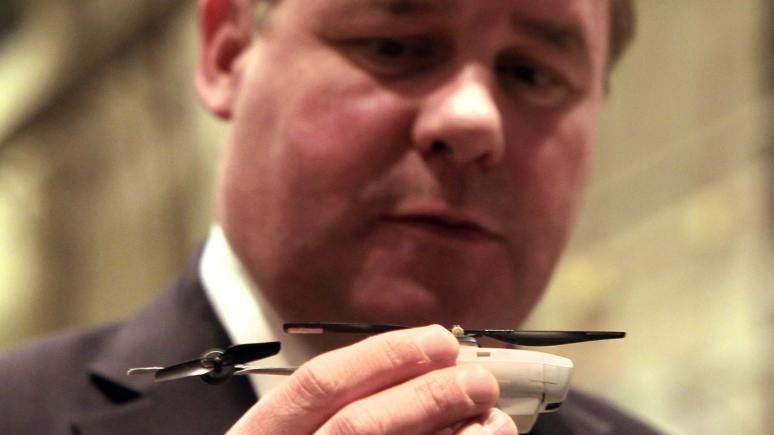 The Armed Forces Minister holds a small Unmanned Aerial Vehicle in his hand. Photo: RAF Waddington