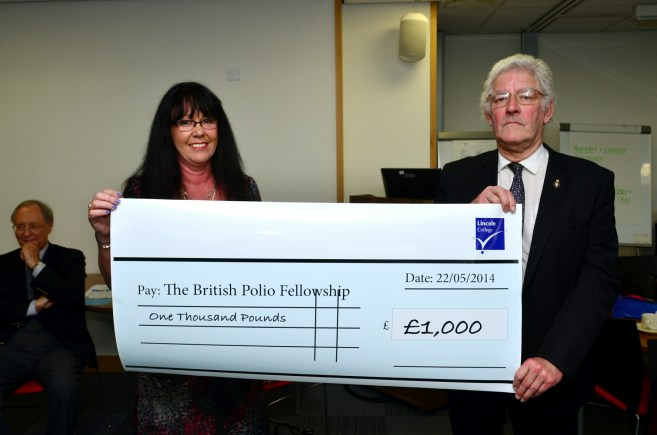 Sarah Adams, Lincoln College Principal's PA, presenting to David Mitchell of Lincolnshire County Chairman of the British Polio Fellowship £1k. Photo: Steve Smailes for The Lincolnite