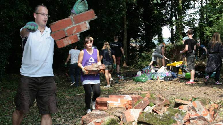 Volunteers clear bricks and debris from the area.