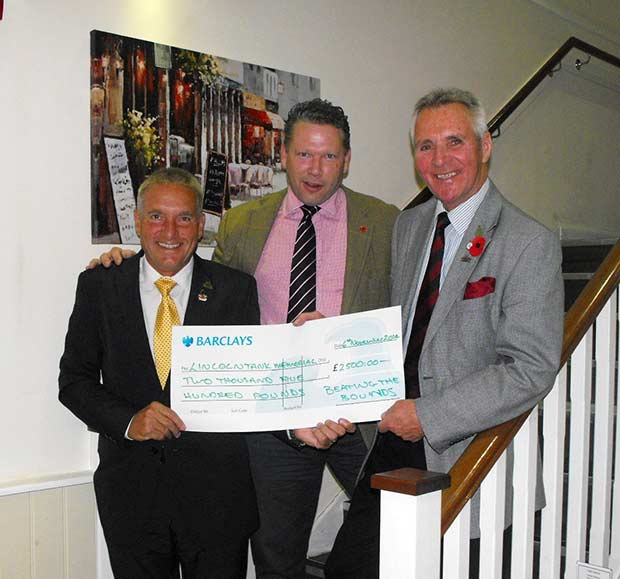 Karl hands over cheque to Lincoln Tank Memorial representatives.