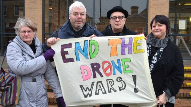 The protesters holding one of the banners they used at RAF Waddington