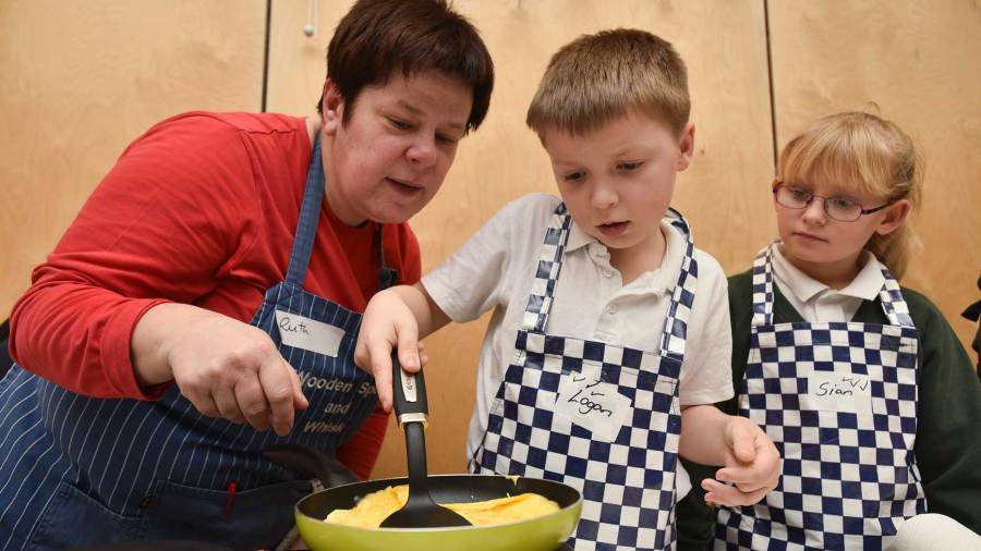 Ruth Wilkinson from Wooden Spoon & Whisk helping a school pupil make an omelette. Photo: Steve Smailes for The Lincolnite
