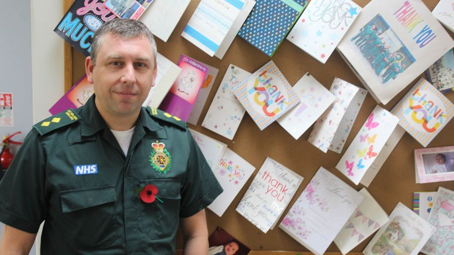 Dominic Ford, Paramedic and Team Leader for North Derbyshire, in front of the thank you letter noticeboard at Chesterfield Ambulance Station.