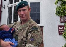 Royal Marines Sergeant Matt Harness cradles his son Spencer in the car park of the Waggon and Horses public house – the very spot where the reservist delivered him. Photo: Royal Marines