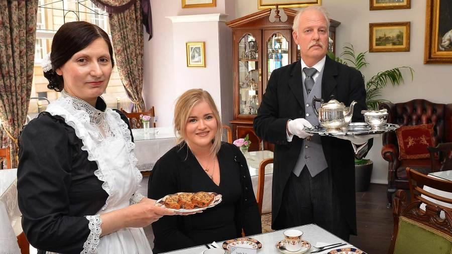 Nikki and Chris Fairey                                      turn maid and butler to serve afternoon tea to (centre) Banks Long & Co Surveyor Harriet Hatcher
