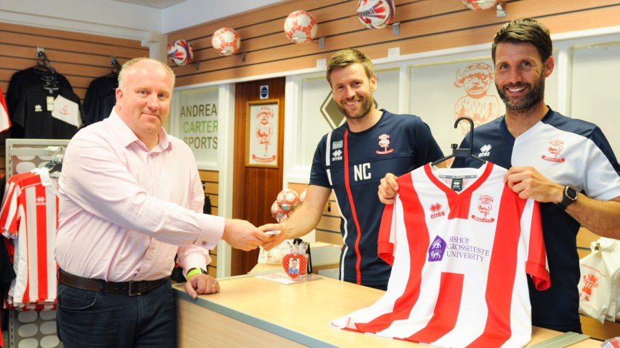 Dr Graham Basten, Head of Social Sciences at BGU, was one of the first in the club shop to buy a new BGU-sponsored shirt from Lincoln City management team Nicky and Danny Cowley. Photo: Emily Bennett / BGU