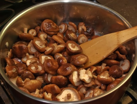 Mushrooms cooking in hte pan Baby Shiitake Mushrooms with Ancho Chile Sauce