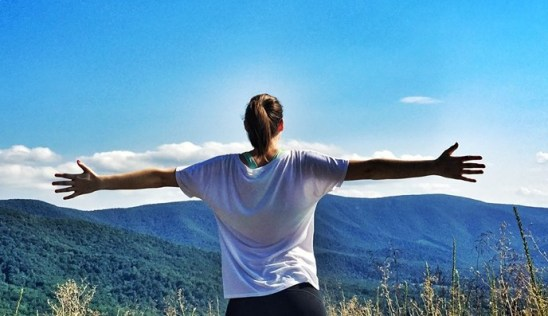 Back view of a woman with her hands up, facing a mountain range.