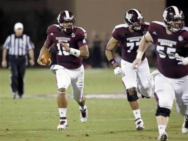 Mississippi State quarterback Dak Prescott (15) follows his blockers Charles Siddoway (77) and Dylan Holley (55) during the second quarter of their NCAA college football game against Troy at Davis Wade Stadium in Starkville, Miss., on Saturday, Sept. 21, 2013. (AP Photo/Rogelio V. Solis)