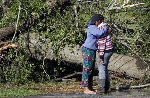 Carnesha Bennett, right, cries on the shoulder of a friend after touring the remains of her mother's child care center in Louisville, Miss., Tuesday, April 29, 2014. The facility was leveled among with a automotive repair shop next door. Numerous businesses, residences and the community hospital were destroyed or heavily damaged after a tornado hit the east Mississippi community Monday. Louisville is the county seat and home to about 6,600 people. (AP Photo/Rogelio V. Solis)