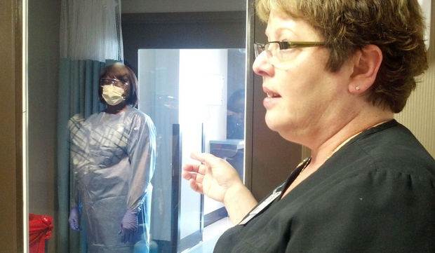 Teresa Aikens, nurse manager of infection control and employee health at the University of South Alabama Medical Center, stands outside of an isolation room as nurse Tamara Taylor, left, demonstrates the procedures that would be used if the hospital were caring for an Ebola patient on Tuesday, Oct. 14, 2014. (Theresa Seiger/tseiger@al.com)