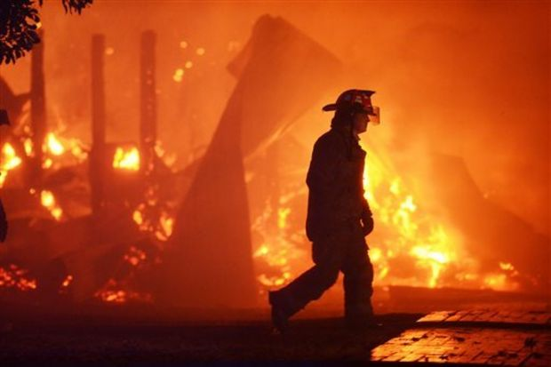 A firefighter walks past blazing wreckage of a barn at the Mississippi Agriculture and Forestry Museum in Jackson, Mississippi, that caught fire late Thursday, Nov. 13, 2014. (AP Photo/The Clarion-Ledger, Joe Ellis)