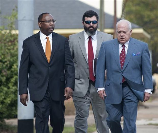 Former Mississippi Corrections Commissioner Chris Epps, left, and his attorney John Colette, right, and Sherwood Colette, arrive at the federal courthouse in Jackson, Miss., Thursday, Nov. 6, 2014. Epps, who resigned abruptly this week, has been charged with accepting hundreds of thousands of dollars in bribes from a Rankin County businessman connected to several private prison companies. (AP Photo/The Clarion-Ledger, Joe Ellis)
