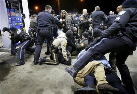 Police try to control a crowd Wednesday, Dec. 24, 2014, on the lot of a gas station following a shooting Tuesday in Berkeley, Mo. St. Louis County police say a man who pulled a gun and pointed it at an officer has been killed. (AP Photo/St. Louis Post-Dispatch, David Carson)