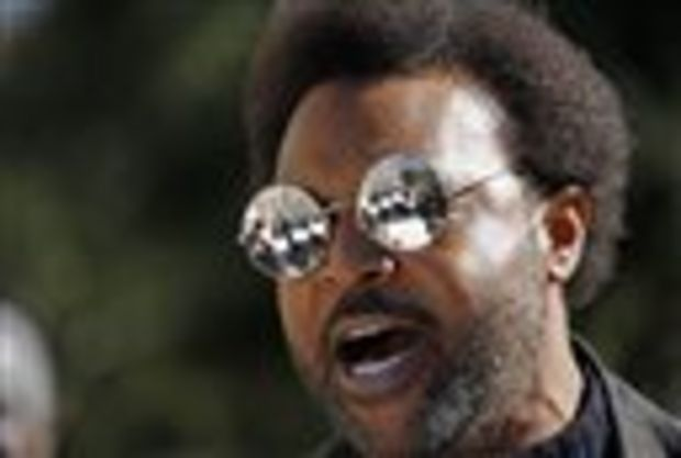 Jackson State University professor C. Leigh McInnis,recites a poem in support of public education and state workers, as protesters holding signs in support are reflected in his sunglass, at a rally on the steps of the Capitol in Jackson, Miss., Tuesday, Jan. 6, 2015. Mississippi lawmakers begin their three-month session and they'll be greeted by diverse groups trying to influence public policy and state funding. (AP Photo/Rogelio V. Solis)