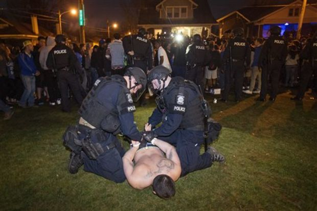 Police arrest a man as Kentucky fans gather near the University of Kentucky campus, Sunday, April 5, 2015, in Lexington, Ky., after Wisconsin defeated Kentucky 71-64 in the semifinals of the NCAA men's college basketball tournament Final Four. (AP Photo/David Stephenson)
