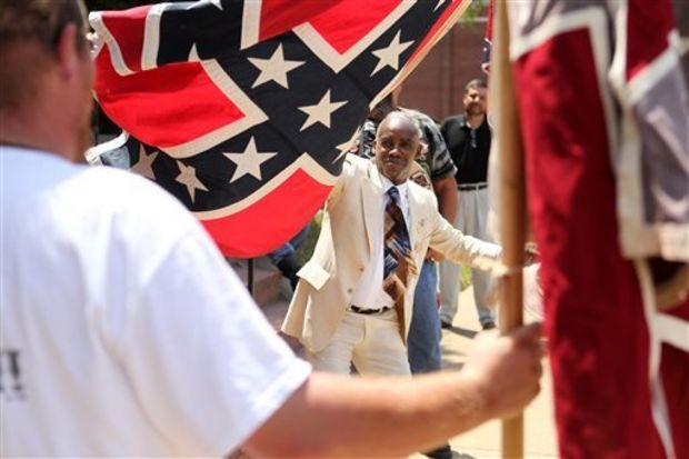 "H.K Edgerton, of Asheville, N.C., waves his Confederate flag as Charles Bodenheimen, foreground, sings ""Dixie"" while standing outside First Baptist Church in Oxford, Miss., as they both honor the late Anthony Hervey during his funeral service Sunday afternoon, Aug. 2, 2015. Hundreds of people, many waving Confederate battle flags outside, gathered for the funeral of Hervey who was killed in an accident near Oxford. Hervey often dressed in Confederate regalia to support the state flag. (Adam Robison/Northeast Mississippi Dailiy Journal)"