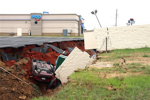 This photo shows vehicles after a cave-in of a parking lot in Meridian, Miss., Sunday, Nov. 8, 2015. Experts are to begin work Monday seeking to determine the cause of the Saturday collapse, authorities said. (Michael Stewart/The Meridian Star via AP)