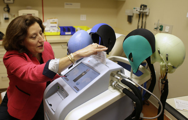 In this July 10, 2013 file photo, Dr. Hope Rugo, an oncologist and breast cancer specialist, demonstrates the use of a Dignitana DigniCap system at the University of California San Francisco Mount Zion Hospital cancer center in San Francisco. The Food and Drug Administration said Dec. 8, 2015, it would allow marketing of the DigniCap to chill patients' scalps - using a cap connected to a cooling machine - as they receive chemo. A study found it significantly reduced hair loss. (Eric Risberg/AP File Photo)