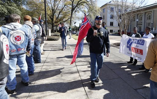 A Mississippi state flag-carrying supporter walks between a small group of counter protestors seeking a change to the current flag, right, and those wanting to keep the Confederate battle emblem on the state flag, on the left, Tuesday, Jan. 19, 2016 at the Capitol in Jackson, Miss. Sons of Confederate Veterans and other groups staged a day-long rally on the grounds of the state Capitol in support of keeping the Confederate battle emblem on the state flag. (Rogelio V. Solis/The Associated Press)