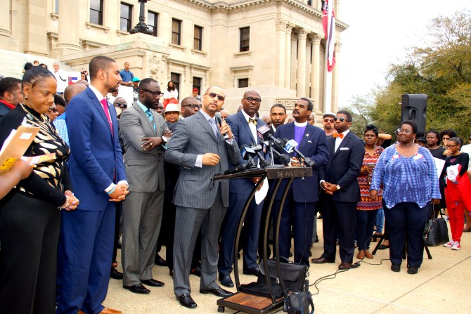 Carlos Moore, (at podium) addresses the crowd during the rally. With him are Rep. Justin Bamberg - S.C., (from left), Jackson Mayor Tony Yarber, Pastor Jamal Bryant and Attorney J. Wyndal Gordon. PHOTO BY JAY JOHNSON