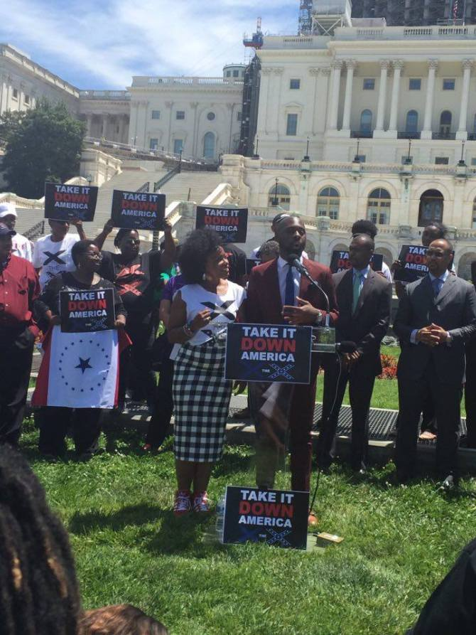 Duvalier J. Malone (at podium) stands next to Actress Aunjunae Ellis during the rally in front of the U.S. Capitol Tuesday.