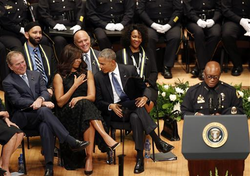 Former President George W. Bush, President Barack Obama and first lady Michelle Obama smile as they react to comments from Dallas Police Chief David Brown during a memorial service at the Morton H. Meyerson Symphony Center in Dallas ,Tuesday, July 12, 2016. Five police officers were killed and several injured during a shooting in downtown Dallas last Thursday night. (Eric Gay/The Associated Press)