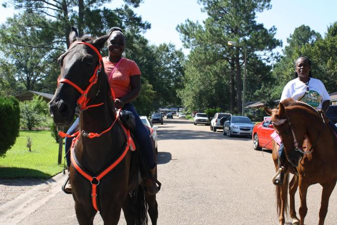 Tina Hobson and Janice Walker ride horses during the community day activities.