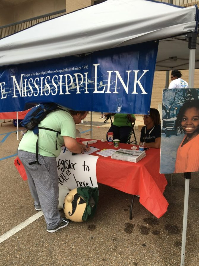 Mississippi Link Publisher Jackie Hampton looks on as a resident registers to vote Sept. 25 in Jackson. PHOTO BY SHANDERIA K. POSEY
