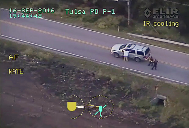 In this photo made from a Sept. 16, 2016 police video, Terence Crutcher, left, with his arms up is pursued by police officers as he walks next to his stalled SUV moments before he was shot and killed by one of the officers in Tulsa, Okla. (Tulsa Police Department via AP)