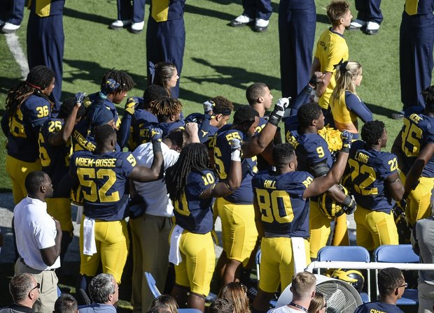 Michigan football players raise their fists up in protest during the national anthem before their game against Penn State. (Junfu Han / AP)