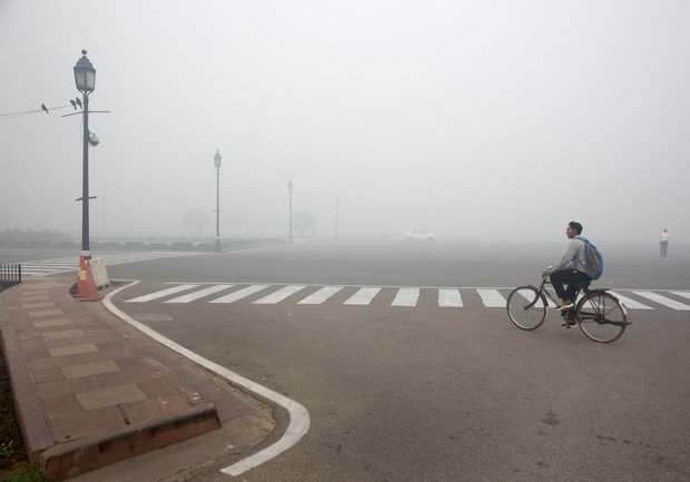 A cyclist rides on a road enveloped by smoke and smog, on the morning following Diwali festival in New Delhi, India. (Manish Swarup / AP)