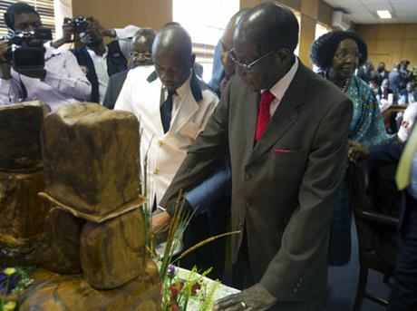 "Zimbabwe's President Robert Mugabe cuts his birthday cake as he marks his 93rd birthday at his offices in Harare, Tuesday, Feb. 21, 2017. Mugabe described his wife Grace, an increasingly political figure, as ""fireworks"" in an interview marking his 93rd birthday. (AP Photo/Tsvangirayi Mukwazhi)"