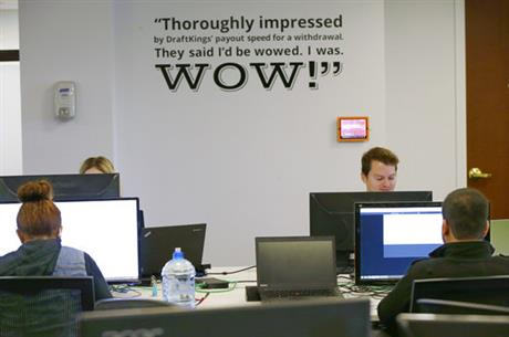 In this Sept. 9, 2015, file photo employees of DraftKings, a daily fantasy sports company, work at their stations in the company's offices in Boston. The daily fantasy sports industry has contracted starkly since questions about the legality of online games offered by companies sparked court and legislative battles across the U.S. last year. (AP Photo/Stephan Savoia, File)