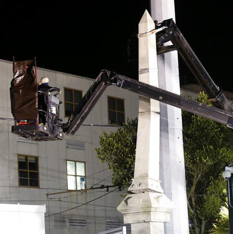 Workers dismantle the Liberty Place monument Monday, April 24, 2017, which commemorates whites who tried to topple a biracial post-Civil War government, in New Orleans. It was removed overnight in an attempt to avoid disruption from supporters who want the monuments to stay. (AP Photo/Gerald Herbert)