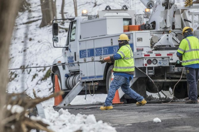 Crew members from PIKE electric company from Maryland pull a downed power line on New Road in Aston, Pa., in order to reconnect it on Thursday, March 8, 2018. Pennsylvania utility companies say more than 110,000 customers are without power following the state's second major snowstorm in less than a week. (Michael Bryant/The Philadelphia Inquirer via AP)