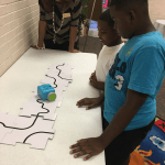 Anne Sanders, branch librarian of the Medgar Evers Library, looks on as Jamarion Atkinson, 9 years old (white shirt) and Darius Johnson, 10 years old (blue shirt) observe robotic toy.