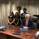 Pam Confer and students from the Hinds County School District stand behind Gov. Bryant at the signing of the declaration.