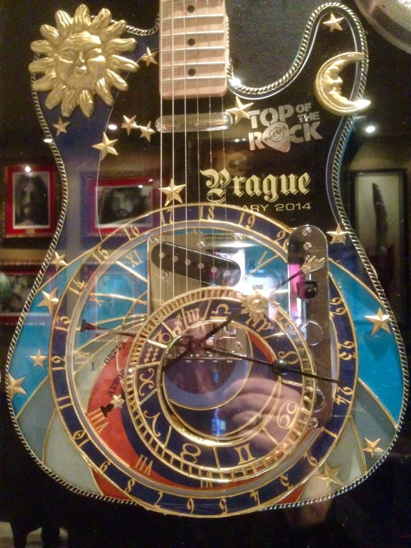 "The ""Astronomical Guitar"" in a display case at Hard Rock, modeled after the Astronomical Clock in Old Town Square, of course, which features statues of the 12 apostles rotating past windows at the top of the clock at the striking of each hour. If the guitar were played, I'd expect statues of Jimmy Page, Eric Clapton and others to roll by."