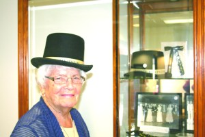 IDA SCHOPP, CURATOR of the Gardner Archives, stands next to a display of the Gardner Centennial of 1954 while wearing a top hat designed for the event. The Archives, located in the Gardner Village Council chambers, contains historical docu- ments and artifacts from Gardner's rich history.