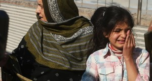 Family members of officials trapped inside the agriculture institute wait outside, during a crackdown operation against militants, in Peshawar, Pakistan, Friday, Dec. 1, 2017. Pakistani police say gunmen have stormed a government complex in the northwestern city of Peshawar, killing an unconfirmed number of people. (AP Photo/Muhammad Sajjad)