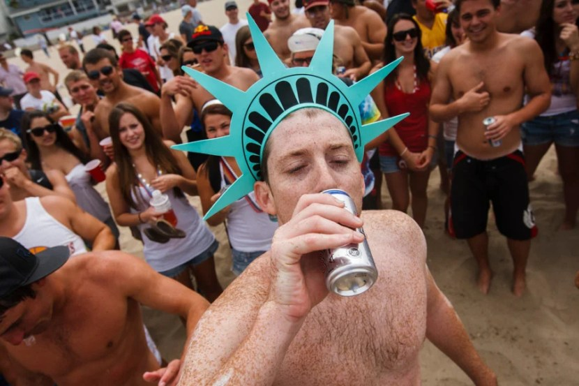 A man drinks a can of beer during the annual Iron Man competition on Saturday, July 4, 2009 in Hermosa Beach, Calif. Competitors haul themselves, flags, and beer into the air to celebrate Independence Day and show their patriotism as part of the Iron Man competition. In the Iron Man, a Hermosa Beach 4th of July tradition for 32 years, participants must run a mile, paddle board a mile, then chug a six-pack of beer, awards are given to those who do not puke Ð and those who puke the best. © 2009 Patrick T. Fallon