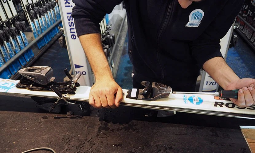 A Ski Dubai employee gets my skis ready to go.