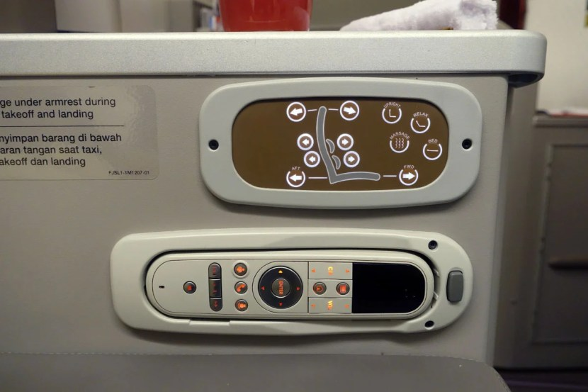 Seat and in-flight entertainment controls.